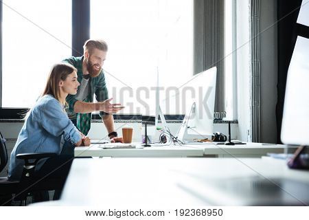 Image of two young smiling colleagues work in office using computers. Looking aside.