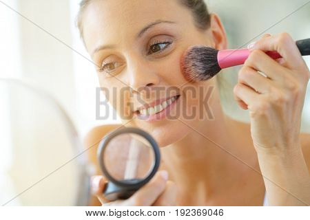 Portrait of beautiful woman putting makeup on