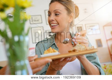 Young woman in restaurant eating fingerfood