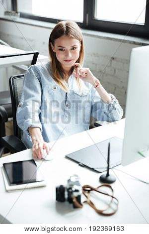 Picture of pretty young woman work in office using computer. Looking at camera.