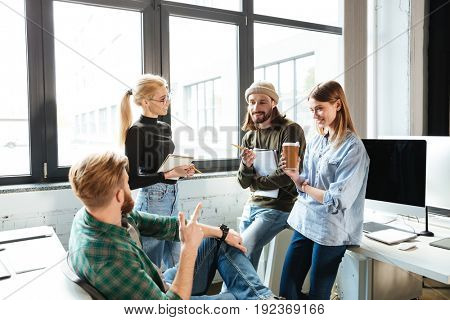 Image of young colleagues standing in office and talking with each other. Looking aside.
