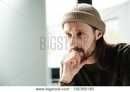 Image of young handsome man in office using computer. Looking aside.
