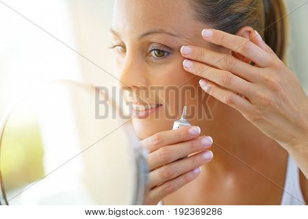 Beautiful young woman applying eye concealer on