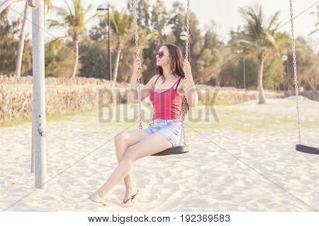 Young european female swinging at Dubai beach. Brunette with long hair in pink top and denim short relaxing at the beach. Vacation concept. Leisure and lifestyle