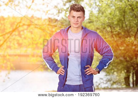 Portrait of confident fit man standing with hands on hips in park