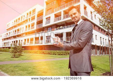 Portrait of confident real estate agent showing office building