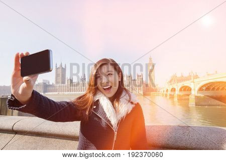 Happy young woman taking self portrait through cell phone against Big Ben at London; England; UK