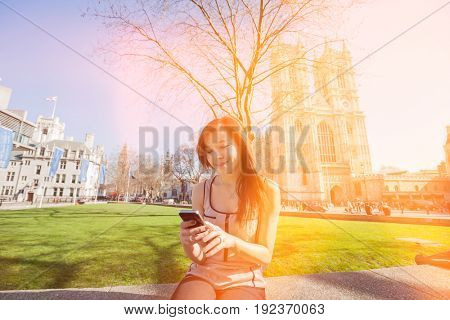 Young woman using cell phone against Westminster Abbey in London; England; UK