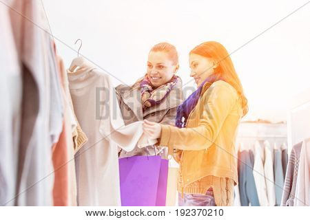 Young female friends choosing sweater in store