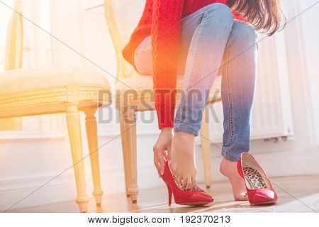 Low section of woman trying on footwear in store