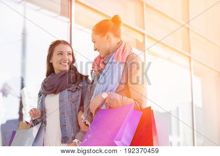 Young female friends looking at each other against store