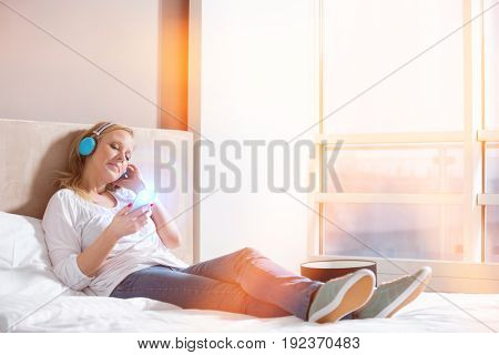 Full length of relaxed woman listening music in bedroom