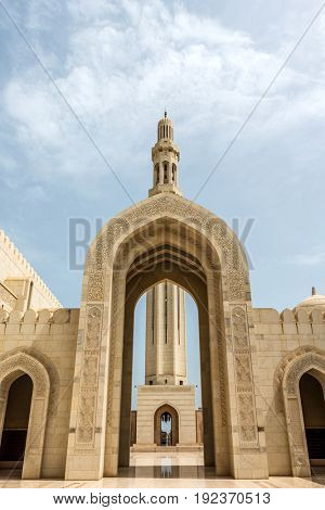 MUSCAT, OMAN - CIRCA AUGUST 2016: ILow Angle Architectural View of Decorative Archways and Minaret at Historical Sultan Qaboos Grand Mosque, Muscat, Oman on Sunny Day with Blue Sky and White Clouds