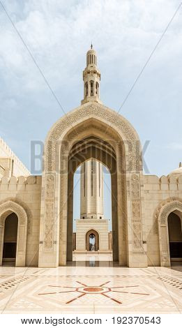 MUSCAT, OMAN - CIRCA AUGUST 2016: ICourtyard and ornately carved stone Arabic arch leading to a tall graceful minaret in the Grand Mosque, Oman, UAE