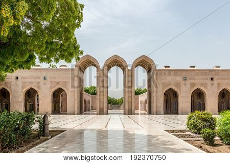 OMAN, MUSCAT - CIRCA AUGUST 2016: Beautiful empty courtyard with arched stone entry way with reflective walkway