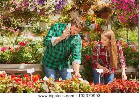 Horizontal outdoors shot of professional gardener communicating with smartphone standing with woman in the garden.