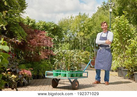 Horizontal outdoors shot of smiling male gardener standing with wagon with potted plants and looking at camera.