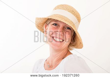 portrait of a attractive blond haired mid aged european woman wearing white dress wearing a summer head showin happy face - head shot - studio shot on white background.