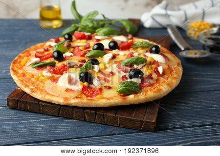 Tasty pizza and its ingredients on wooden table