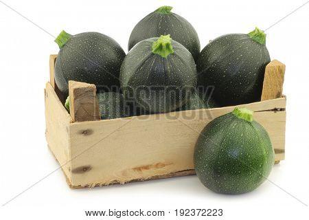 Green zucchini's (Cucurbita pepo) in a wooden crate on a white background