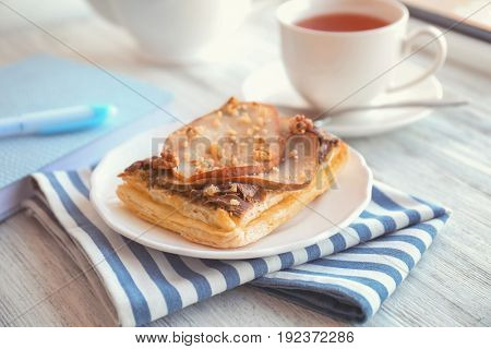 Plate with delicious pastry and striped napkin on wooden table