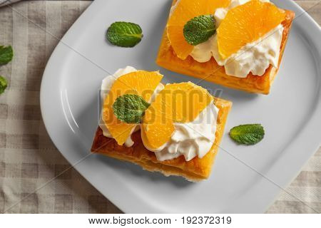 Tasty puff pastry dessert with orange and whipped cream on plate