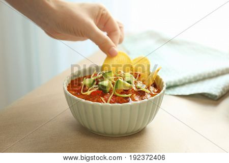 Woman putting chips into bowl with chili turkey, closeup