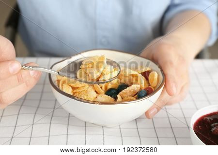 Person eating tasty corn flakes for breakfast at table