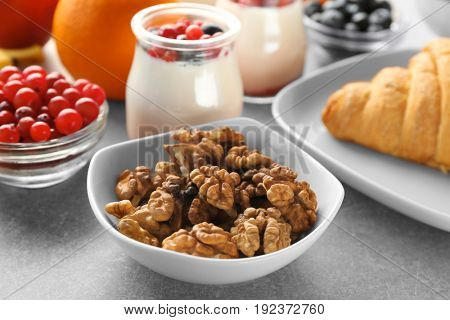 Bowl with nuts and served breakfast on table