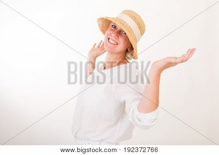 portrait of a attractive blond haired mid aged european woman wearing white dress and a beige summer head showin happy face - half body - studio shot on white background.
