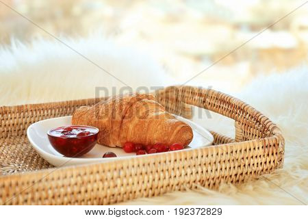 Wicker tray with plate and delicious breakfast on fluffy surface