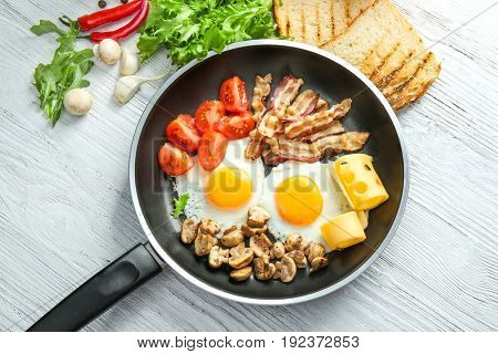 Frying pan with tasty eggs, bacon and mushrooms on table