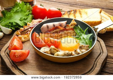 Frying pan with tasty egg, bacon and sausage on table