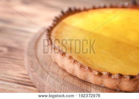 Plate with tasty lemon curd pie on wooden table, closeup