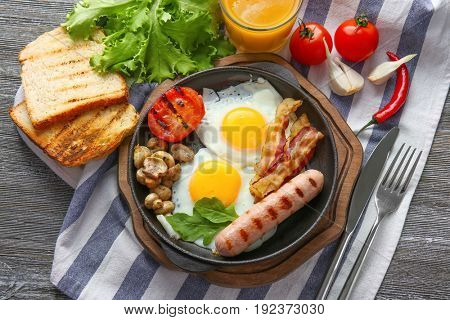 Frying pan with tasty eggs, bacon and sausage on table