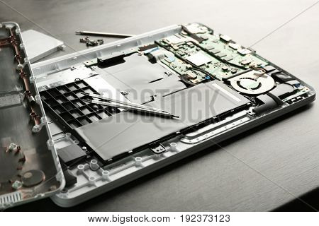 Dismantled laptop with tools on table. Concept of computer repair