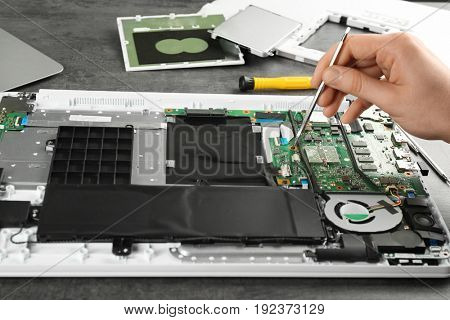 Man fixing dismantled laptop on table. Concept of computer repair