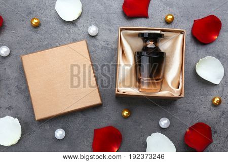 Perfume in present box on gray background