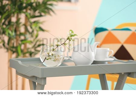 Tea set and vase with beautiful flowers on table at home