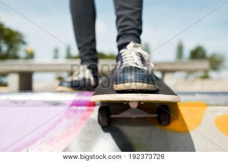 closeup of a young caucasian man skateboarding in an outdoors skate park