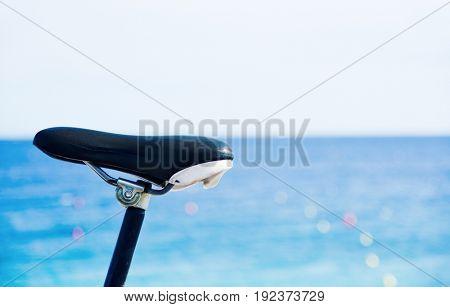closeup of a bicycle parked next to the sea, with a blank space on top
