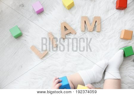 Legs of cute baby and word LIAM composed of wooden letters on floor. Choosing name concept