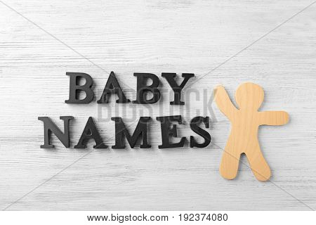 Black letters BABY NAMES and wooden figure on table