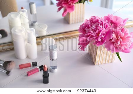 Beautiful bouquet with fragrant peonies and cosmetics on dressing table near mirror