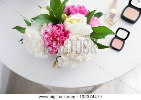 Beautiful bouquet with fragrant peonies and cosmetics on dressing table