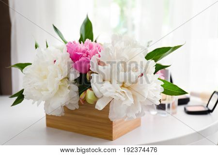 Beautiful bouquet with fragrant peonies on dressing table