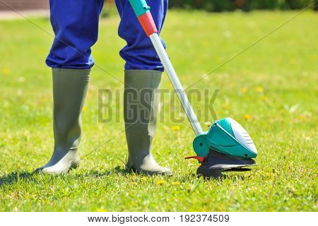 Young worker mowing lawn with grass trimmer outdoors on sunny day, closeup