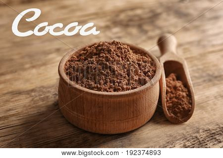Bowl and scoop with cocoa powder on wooden background
