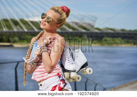 beautiful young blond woman with braid over city bridge. The feet high socks and roller skates.