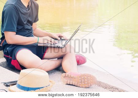 Asian man in casual clothing using laptop in public park Lifestyle and Business concept
